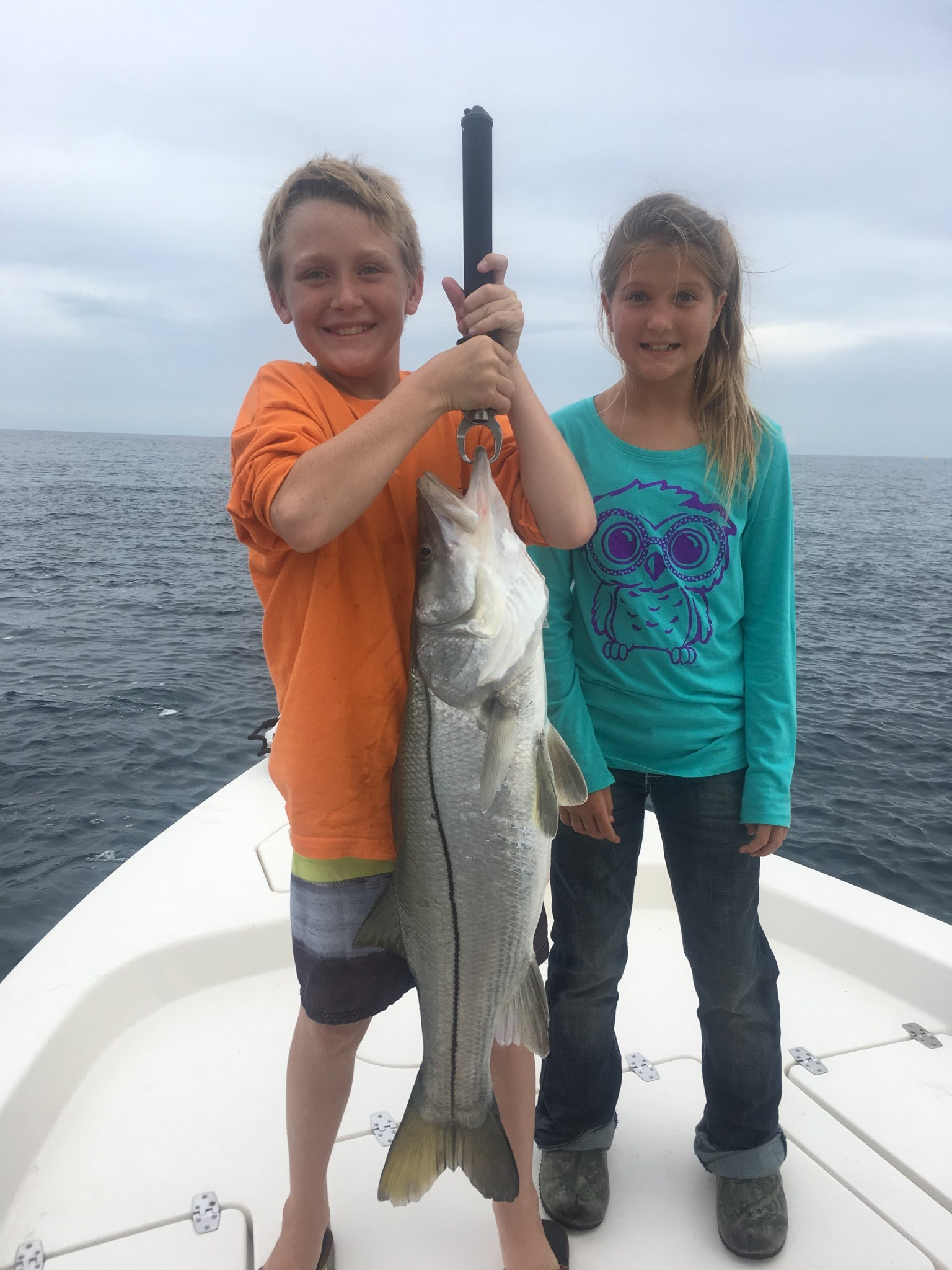 kids holding large fish